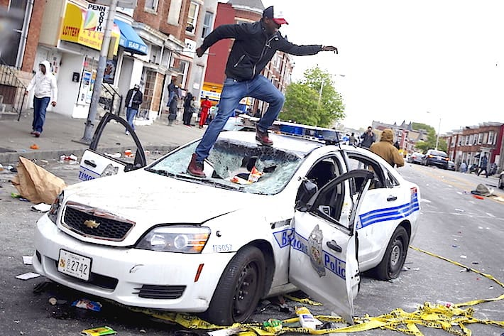 Demonstrators jump on a damaged Baltimore police department vehicle during clashes in Baltimore, Maryland April 27, 2015. Several Baltimore police officers were injured on Monday in violent clashes with young people after the funeral of a black man, Freddie Gray, who died in police custody, and local law enforcement warned of a threat by gangs. REUTERS/Shannon Stapleton - RTX1AJR0
